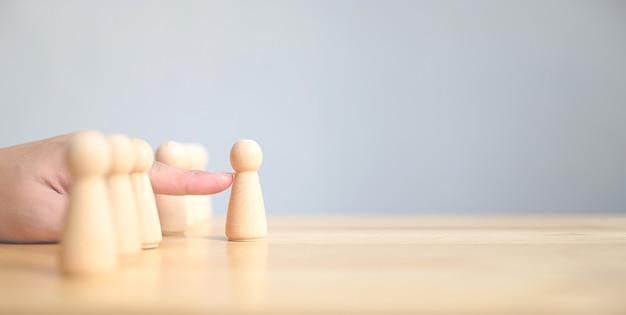 Hand kiest een houten volk dat opvalt tussen de massa
