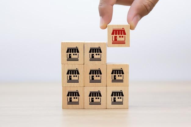 Hand kiezen houten blog met franchise pictogrammen winkel