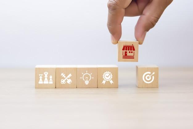 Hand kiezen houten blog met franchise pictogrammen winkel.