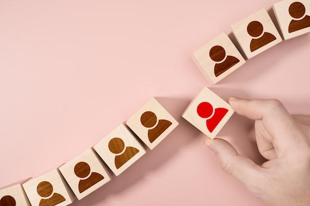Hand kiezen van een houten persoonsblok uit een set. werkgelegenheid keuze concept