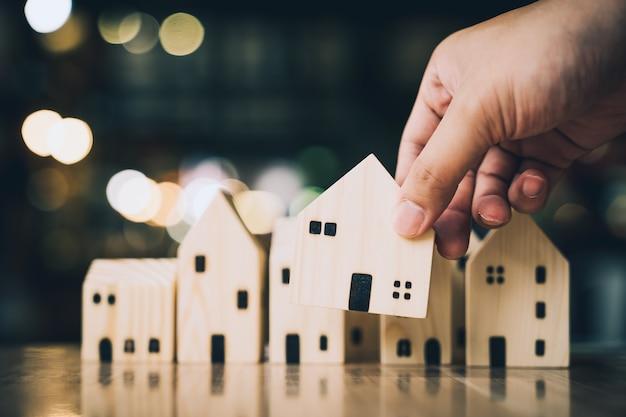 Hand kiezen van mini houten huismodel uit model