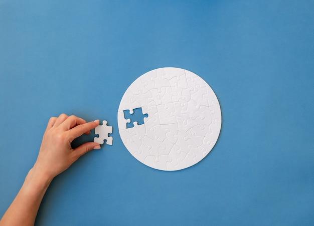 Hand laatste stukje aanbrengend witte ronde puzzel