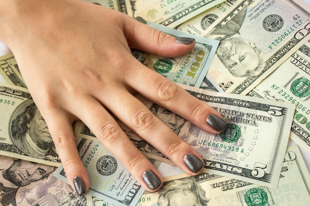 Hand liggend op dollarbiljetten