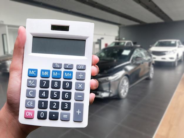 Hand man dringende rekenmachine voor zakelijke financiën op auto showroom wazig