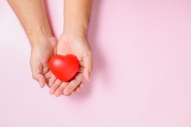 Hand man met rood hart, donatie, gelukkige vrijwilligers liefdadigheid, mvo sociale verantwoordelijkheid, wereldhartdag, wereldgezondheidsdag, wereld geestelijke gezondheidsdag concept