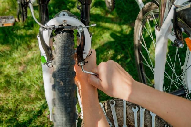 Hand man vaststelling fietswiel met handen buiten, close-up.