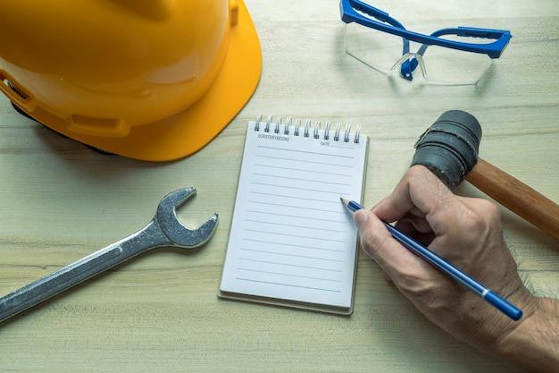 Hand mensen man met blocnote voor het controleren van fabriek of industrie op bureau voor het schrijven van notities inspecteur.