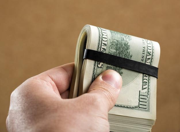 Hand met $ 100 bankbiljetten
