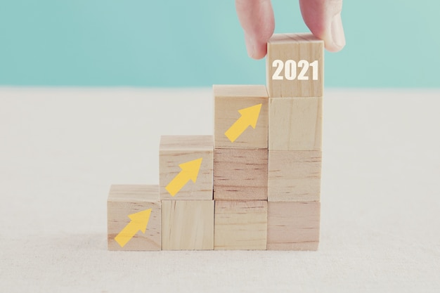 Hand met 2021 en pijlenladder omhoog op houten blokken