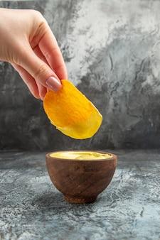Hand met aardappelchip in een kleine mayonaisekom op grijze tafel verticale weergave