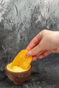 Hand met aardappelchips in een kleine kom mayonaise op grijze tafel