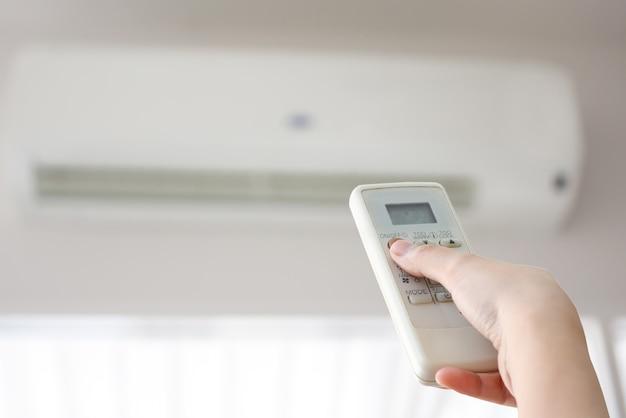 Hand met afstandsbediening gericht op airconditioner