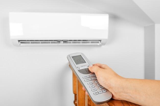 Hand met afstandsbediening gericht op de conditioner aan de muur