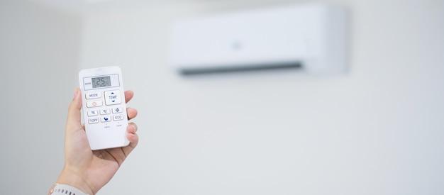 Hand met afstandsbediening voor het aanpassen van de airconditioning in de kamer thuis