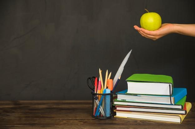 Hand met appel op de werkplek met boeken en briefpapier