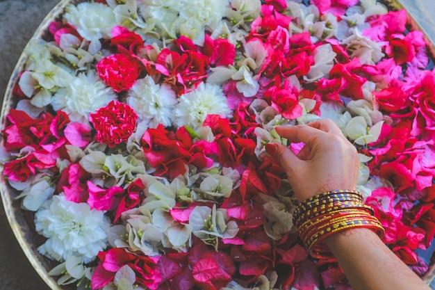 Hand met armbanden halen kleurrijke bloemen op het water