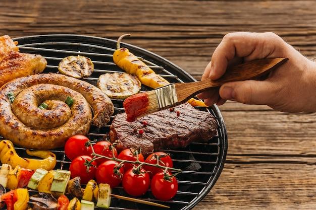 Hand met bedruipende borstel marinate vlees bij de grill