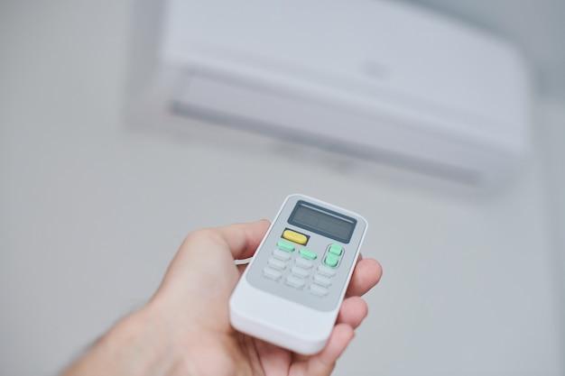Hand met behulp van airconditioning afstandsbediening