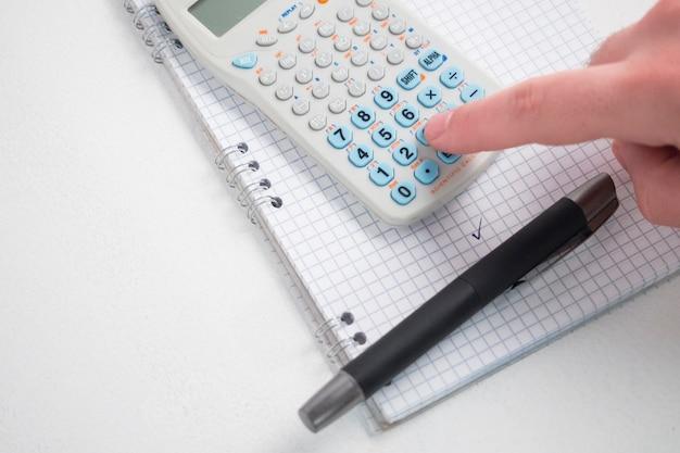 Hand met behulp van calculator op bureau