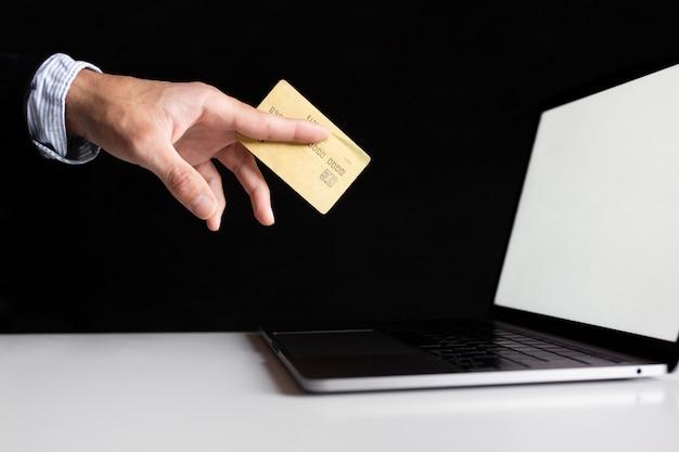 Hand met behulp van een kaart om online te kopen met laptop