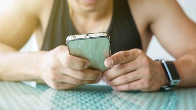 Hand met behulp van een smartphone en een smartwatch.