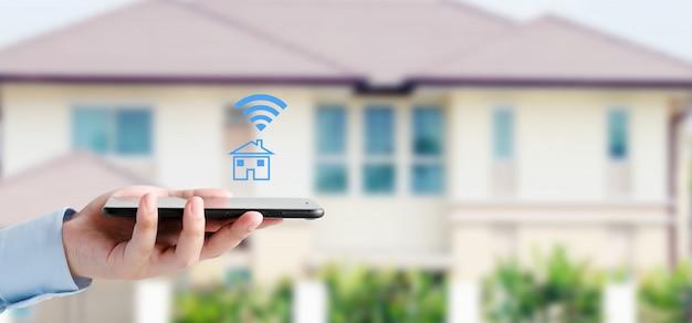 Hand met behulp van slimme telefoon met slimme home control pictogram op vervagen huis achtergrond