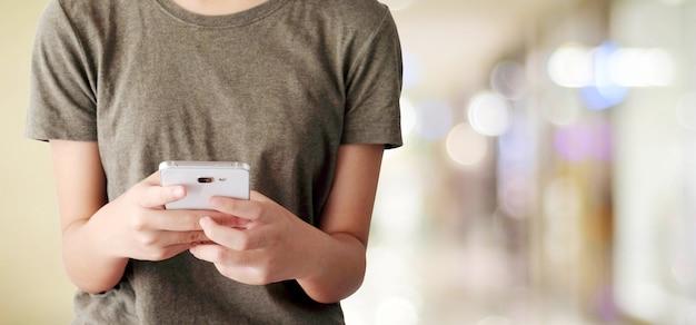 Hand met behulp van slimme telefoon over onscherpte winkel met bokeh lichte achtergrond