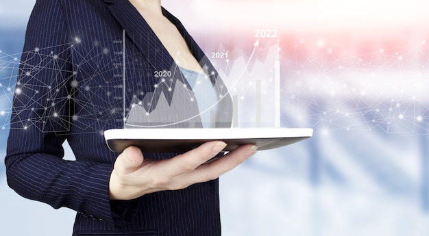 Hand met behulp van tablet die verkoopgegevens en economische groeigrafiek analyseert. hand houden witte tablet met digitale hologram groei grafiek grafiek teken op lichte onscherpe achtergrond. bedrijfsstrategie.