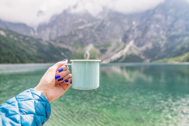 Hand met beker, kristalhelder meer sea eye en bergen in tatra national park, polen