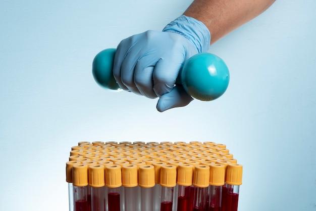 Hand met beschermende nitrilhandschoen die gewicht vasthoudt voor fysieke activiteit met bloedafnamebuisjes.