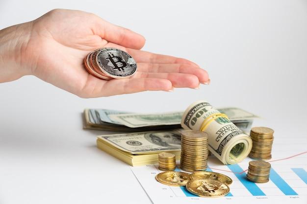 Hand met bitcoin boven geldstapel