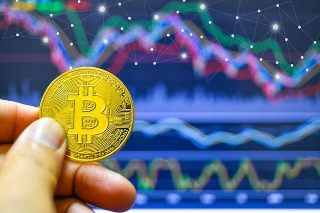Hand met bitcoin op een achtergrond van groeigrafiek op een scherm of laptop