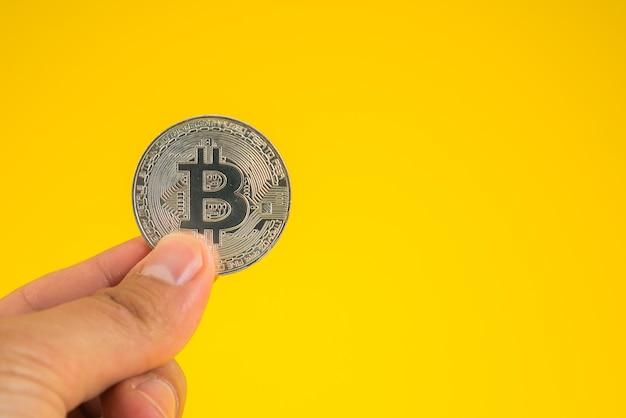 Hand met bitcoin tussen vingers op gele achtergrond.