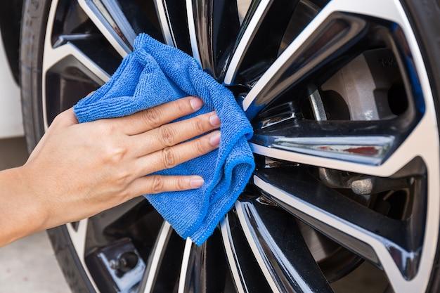 Hand met blauw microfiber doek schoonmaak auto wiel.