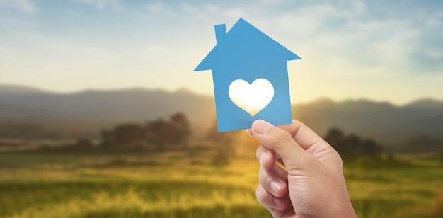 Hand met blauw papieren huis met hartvormig raam op landschapsachtergrond