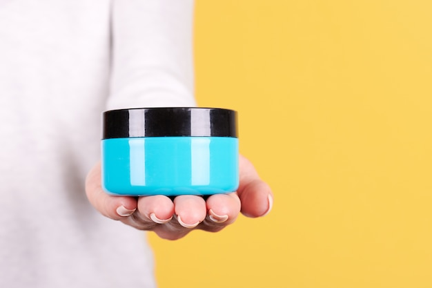 Hand met blauwe crème pot geïsoleerd