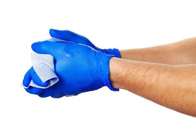 Hand met blauwe handschoenen neemt een witte doek