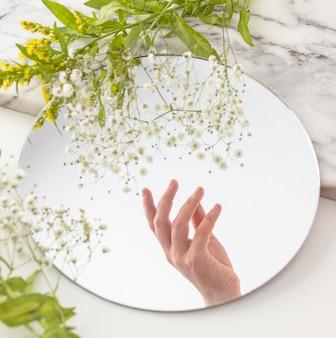 Hand met bloemen in spiegel