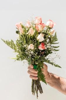 Hand met boeket rozen