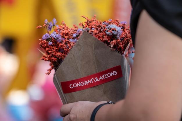 Hand met boeket van gedroogde oranje bloemen verpakt in papier