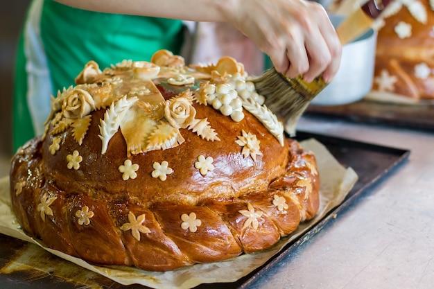 Hand met borstel raakt brood. brood op ovenschaal. vers gekookt huwelijksbrood. eten voor de gasten van de ceremonie.