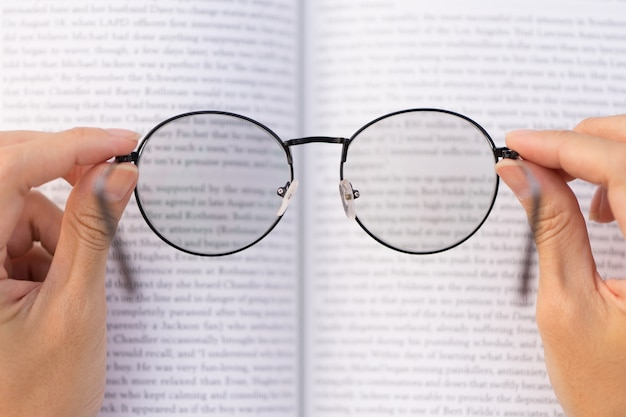 Hand met bril met boek