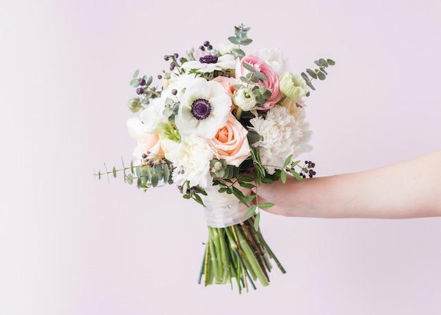 Hand met bruiloft boeket