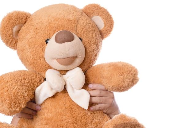 Hand met bruine schattige pluizige teddybeer als een geschenk