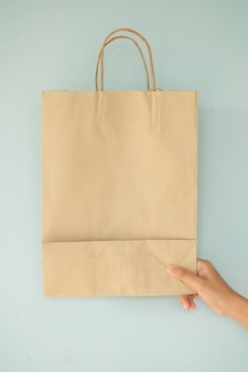 Hand met bruine tas