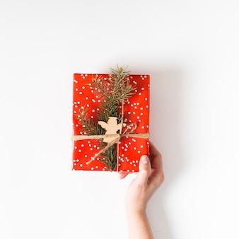 Hand met cadeaupapier omwikkeld met rood papier