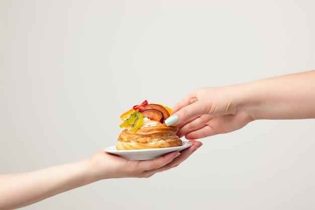 Hand met cake met vers fruit op grijs