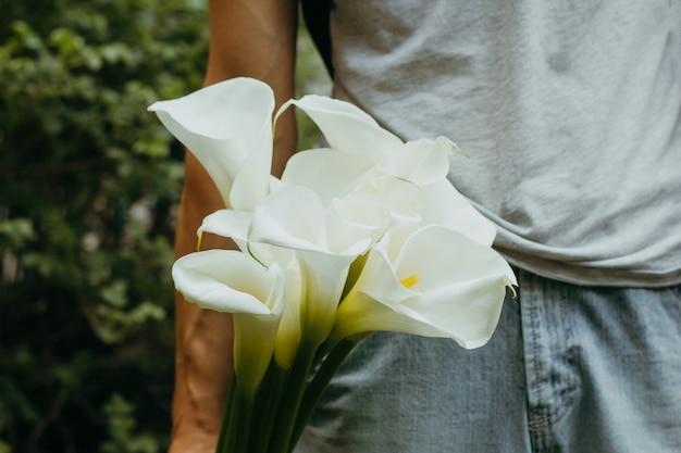 Hand met calla lelies bloemen