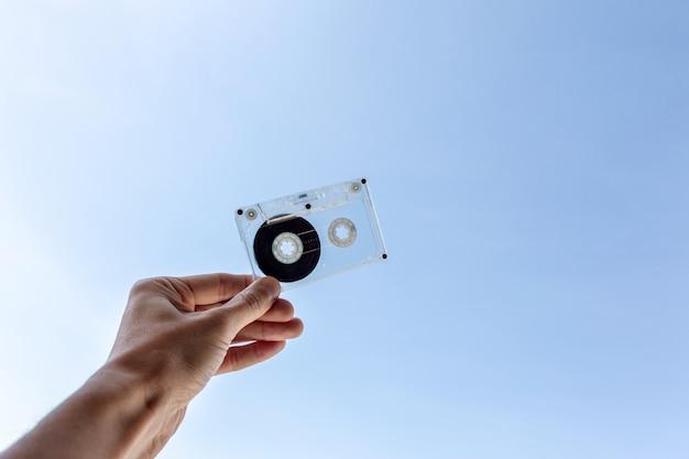 Hand met cassettebandje op blauwe hemel