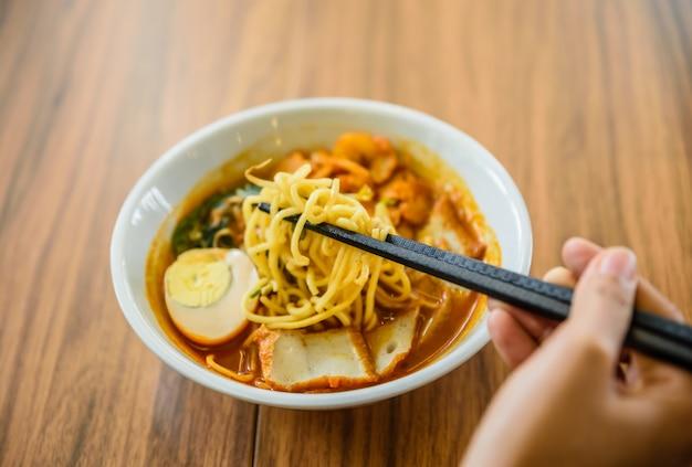 Hand met chinese eetstokjes die noedel eten